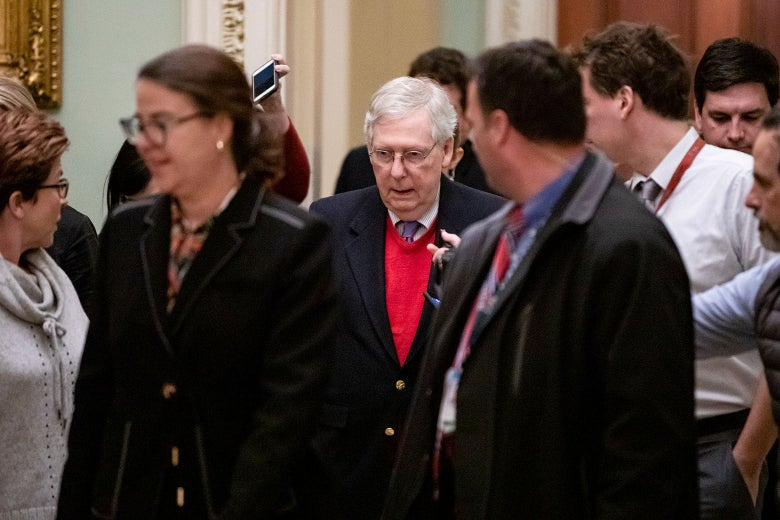 Senate Majority Leader Mitch McConnell is flanked by reporters holding out smartphones and asking him questions.