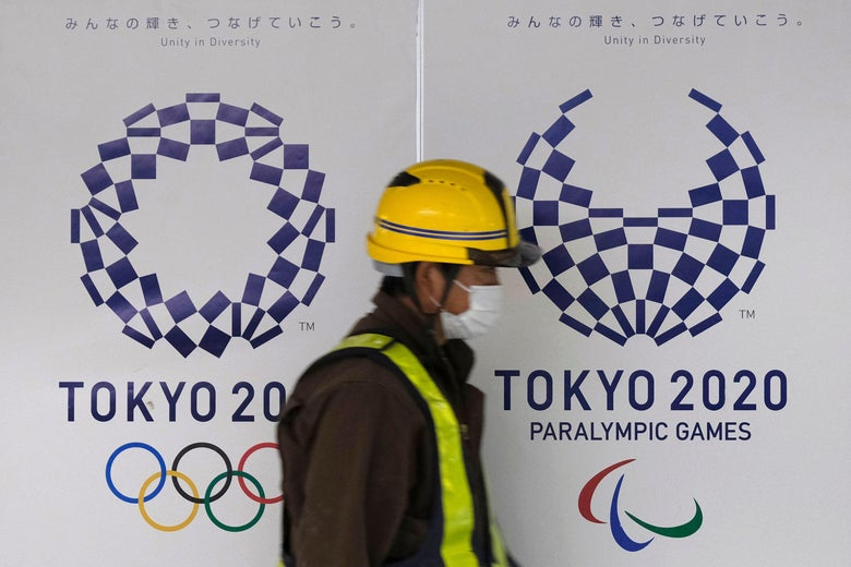 A worker wearing a mask walks by the logo of the Tokyo 2020 Olympic Games and Paralympic Games.