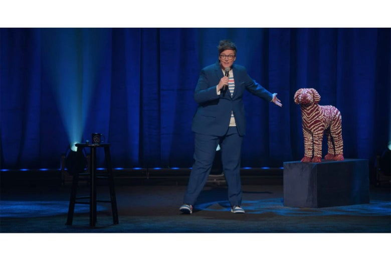 Hannah Gadsby on stage in a still from Douglas, gesturing at a statue of a zebra-striped dalmatian made from crayons.