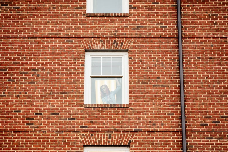 A young woman viewed through her window in a brick building.