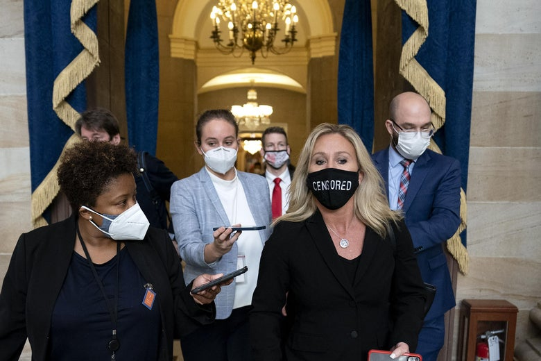"Marjorie Taylor Greene wears a protective mask reading ""CENSORED"" while walking with others in the Capitol."