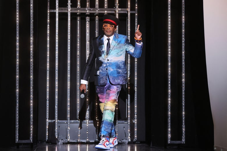 Spike Lee walks out on a stage wearing a suit of rainbow colors.