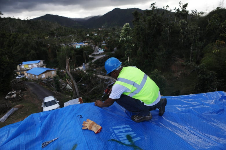 MOROVIS, PUERTO RICO - DECEMBER 20:  A contractor helps apply a FEMA tarp to a home damaged by Hurricane Maria on December 20, 2017 in Morovis, Puerto Rico. Barely three months after Hurricane Maria made landfall, approximately one-third of the devastated island is still without electricity and 14 percent lack running water. While the official death toll from the massive storm remains at 64, The New York Times recently reported the actual toll for the storm and its aftermath likely stands at more than 1,000. Puerto Rico's governor has ordered a review and recount as the holiday season approaches.  (Photo by Mario Tama/Getty Images)