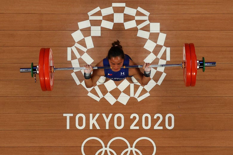 An overview of a female weightlifter midway through a barbell lift, with the Tokyo 2020 Olympics logo underneath her feet.