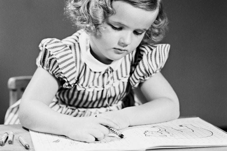 Old black-and-white photo of a little girl coloring in a coloring book