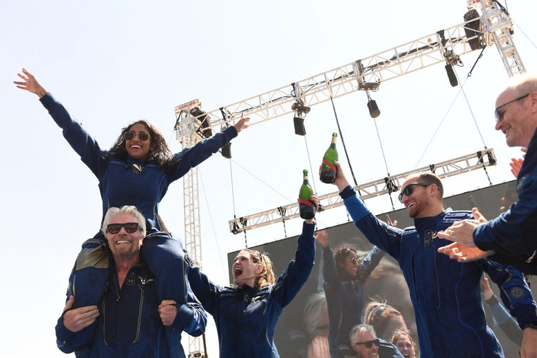 Virgin Galactic founder Sir Richard Branson(L), with Sirisha Bandla on his shoulders, cheers with crew members after flying into space aboard a Virgin Galactic vessel, near Truth and Consequences, New Mexico on July 11, 2021.