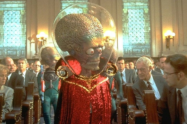 An alien with a giant head, wearing a glittery red robe and bubble helmet, walks down an aisle surrounded by people in suits.
