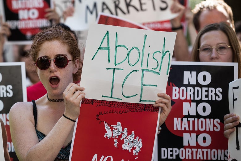 """A protester holds a sign that says, """"Abolish ICE"""""""