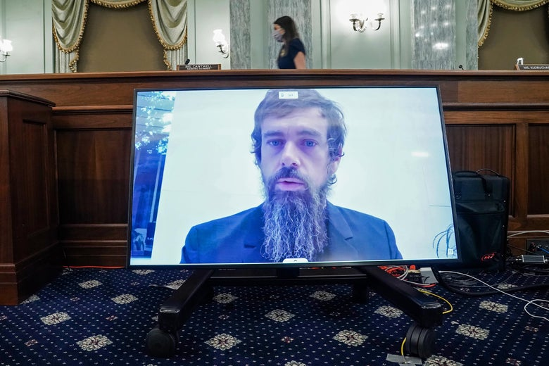 Jack Dorsey appears with unkempt hair and a long, scraggly brown and gray beard on a screen sitting on the floor of a Senate hearing room