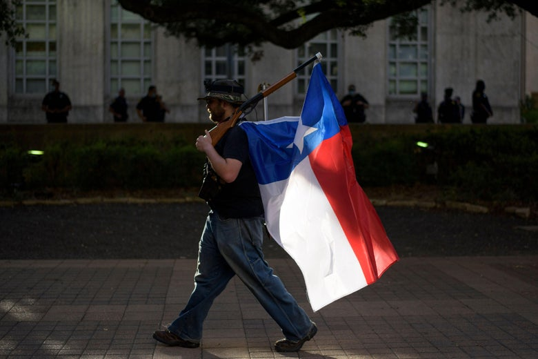 A man walks with a rifle with a Texas flag attached to it during a Police Appreciation rally at the City Hall in Houston.