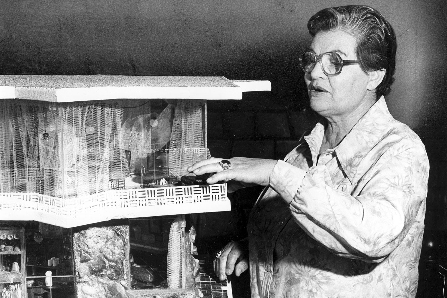 A black-and-white photo of Frances Gabe with a model of her self-cleaning house system.