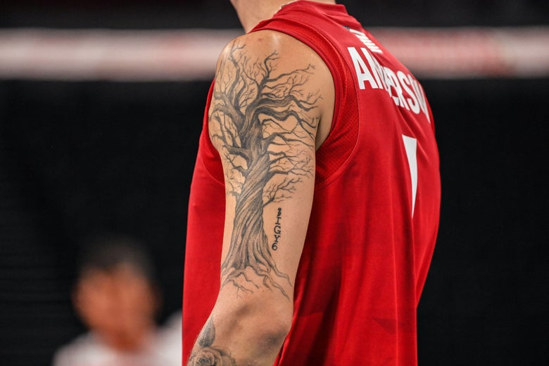 Anderson's left arm with a large twisted leafless tree tattoo on it, in tank uniform for indoor volleyball