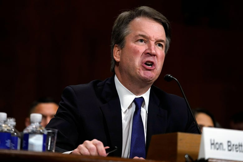Brett Kavanaugh scrunches up his face as he shouts into the microphone on a table.