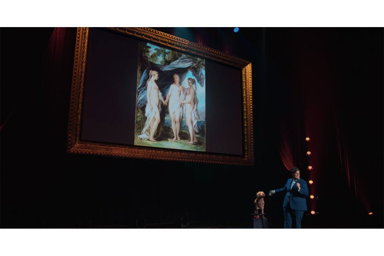Hannah Gadsby, in a blue suit, on stage in front of a painting of three naked women.
