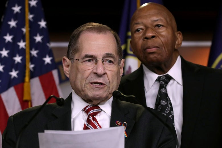 Nadler, holding papers, speaks into a microphone while Cummings stands behind him.