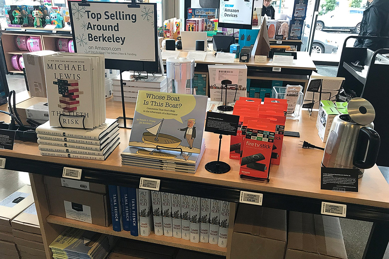 "A sign says ""Top Selling Around Berkeley"" over books by Michael Lewis, a Fire TV Stick, and other items."