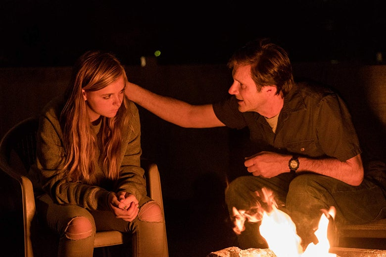 In a still from Eighth Grade, Elsie's father tries to comfort her as they sit in front of a campfire.