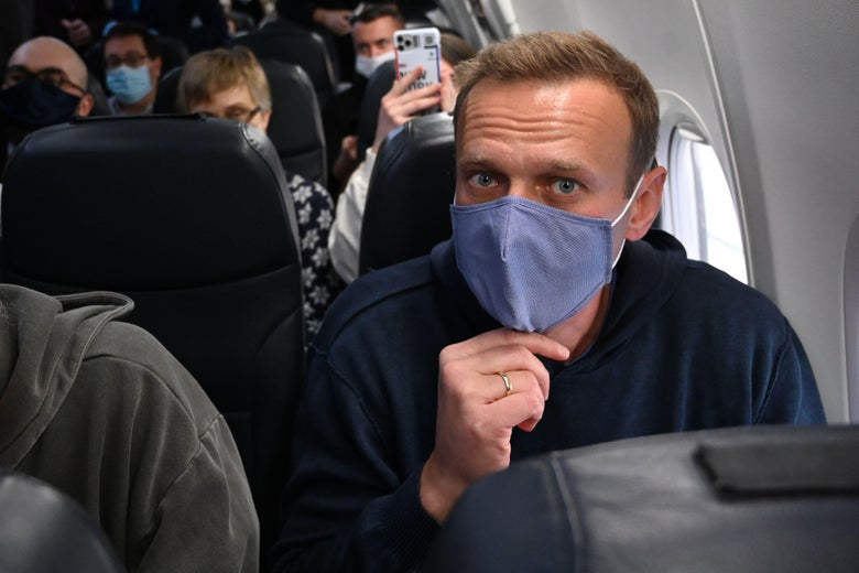 Navalny seated in a full airplane cabin, wearing a cloth mask and looking at the camera
