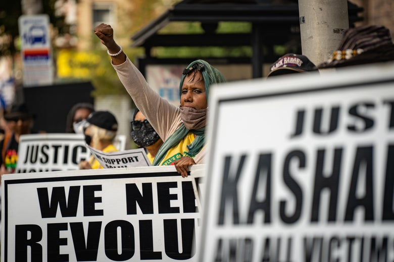 A woman with a sign raises her fist as a crowd gathers at a People's Organization for Progress rally to protest police brutality on August 17, 2020 in Newark, NJ.