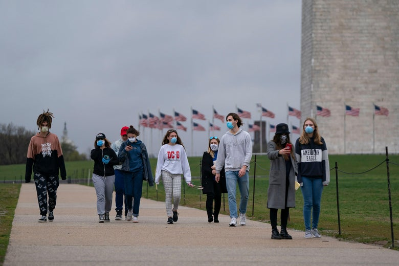 A group of young people wear protective masks as they walk near the Washington Monument.