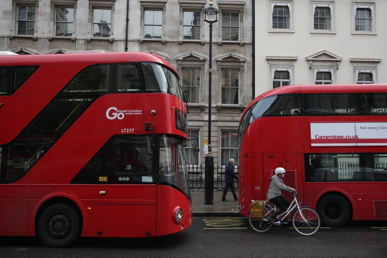 A cyclists passes between red London double-decker buses in central London on November 20, 2017.