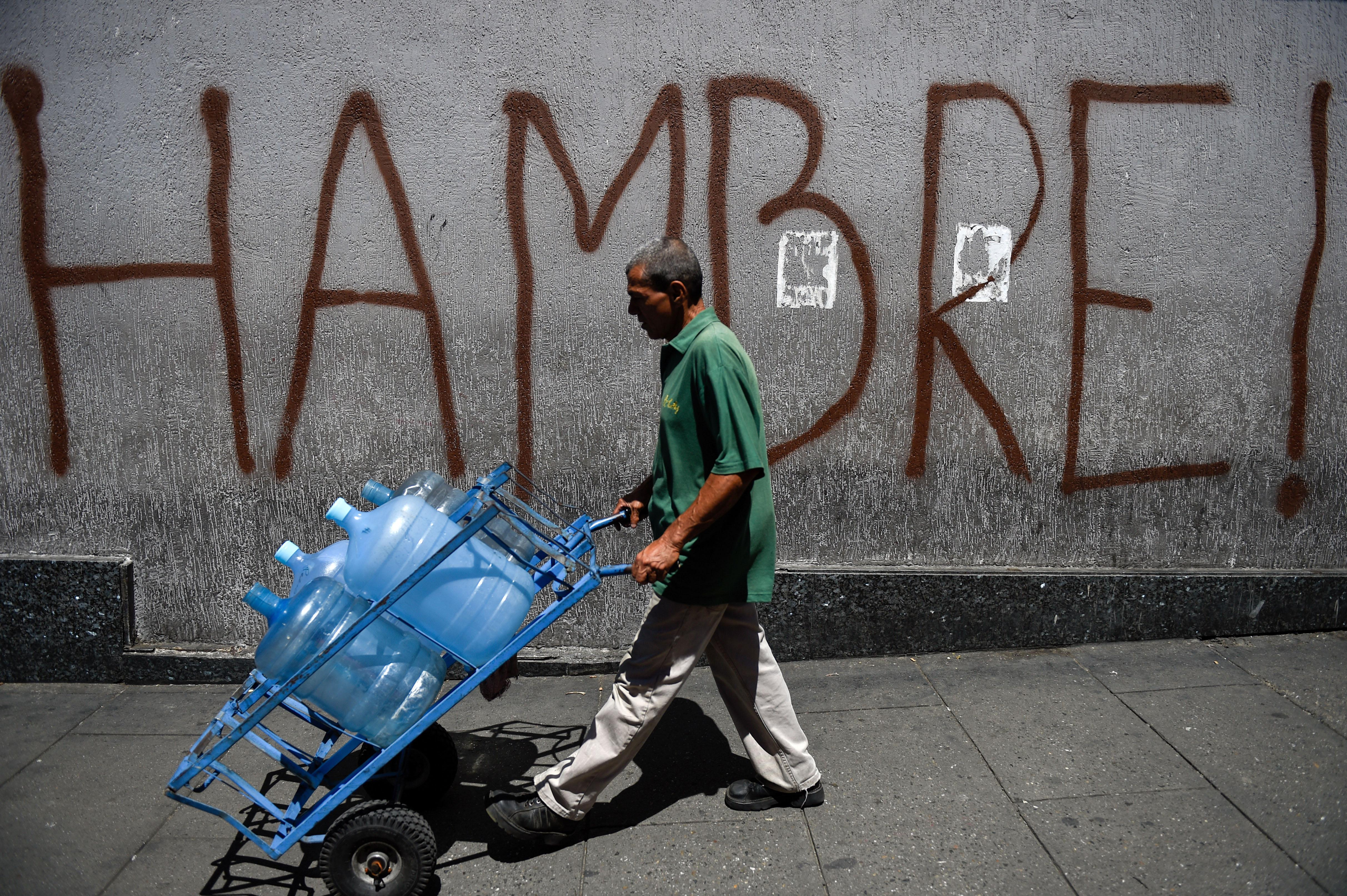 """A Venezuelan man pushes a hand truck loaded with water jugs in front of street graffiti reading """"HAMBRE!"""" or """"hungry"""" in Spanish."""
