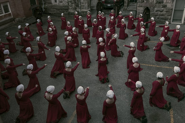 View from above: Women wearing red robes and white bonnets kneel in concentric circles, each with one arm outstretched.