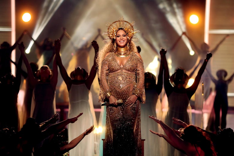 Beyonce standing on stage smiling in a long sleeve gold dress and a halo crown.