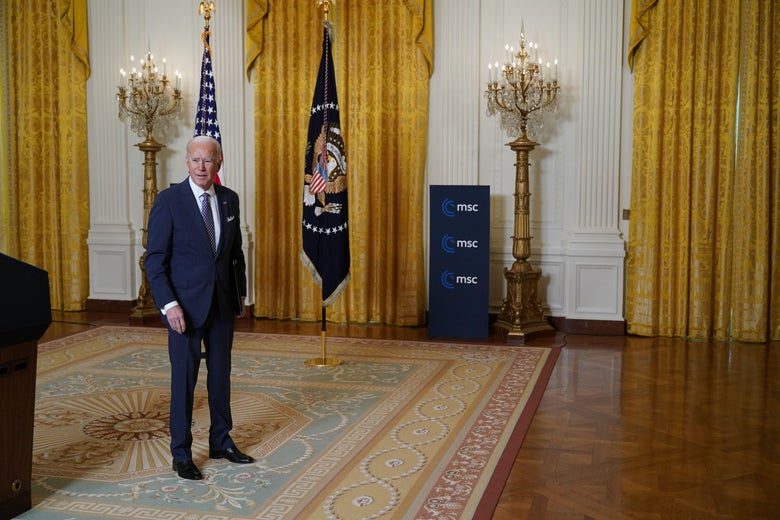 Biden stands in the East Room of the White House.