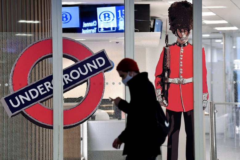 A person wearing a mask and looking at their phone walks past a London Underground sign and a Queen's Guard standee at the closed entrance of the Eurostar terminal at Brussels South railway station.