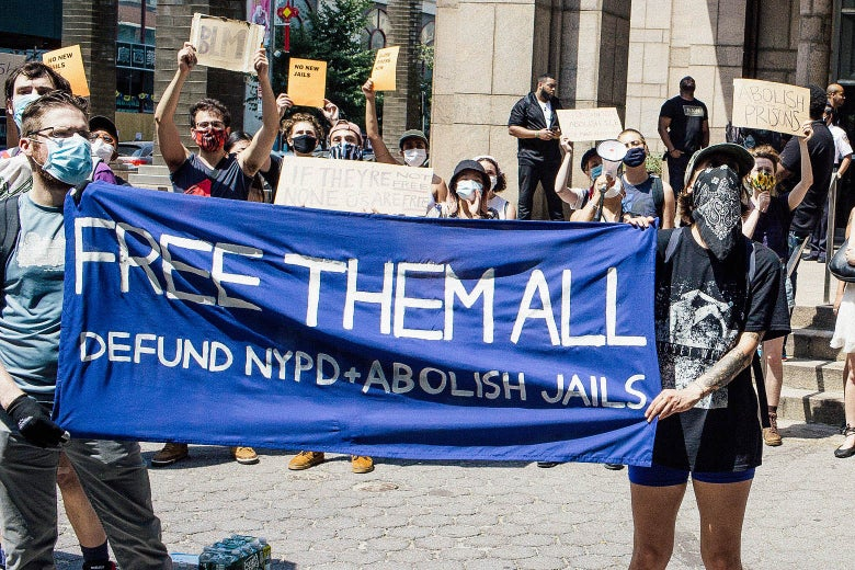 "Criminal justice reform activists hold up signs that say ""no new jails,"" ""free them all,"" and ""abolish prisons."""