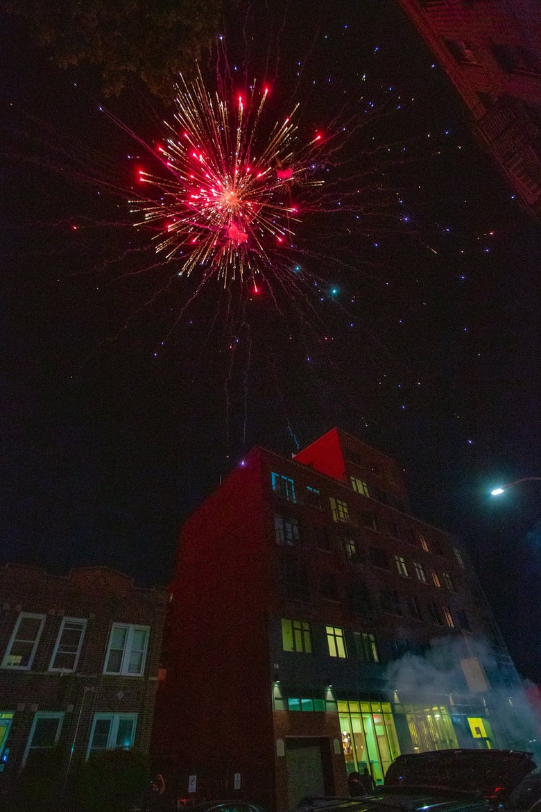A large red firework explodes over an apartment building in Brooklyn New York
