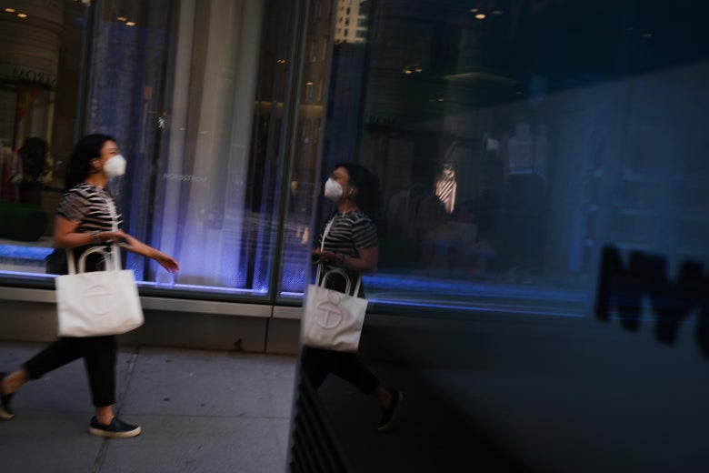 """A woman wearing a mask walks by a sign that says """"NYC."""""""