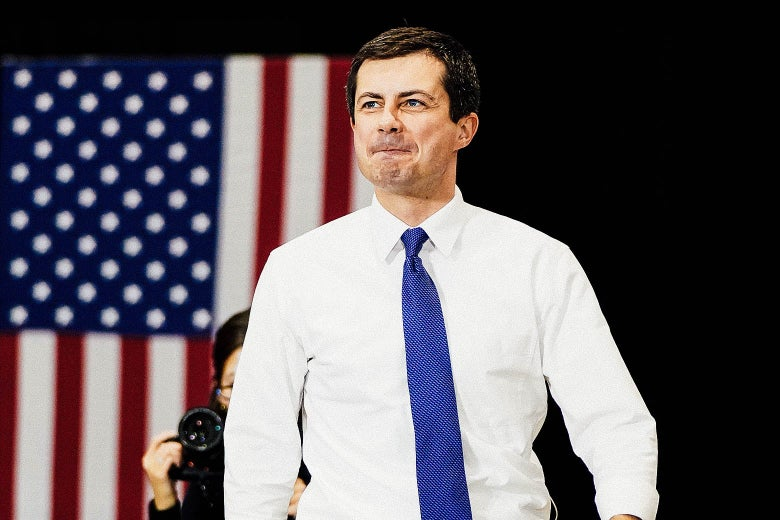 Buttigieg smiling as he walks, with an American flag in the background.