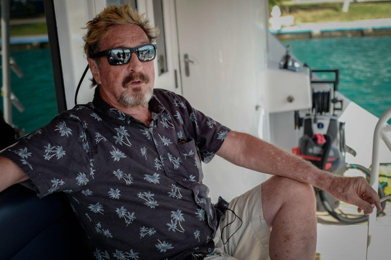 McAfee, wearing sunglasses, smokes a cigarette while sitting on the deck of his yacht that is anchored at a marina.