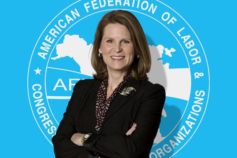 Elizabeth Shuler crosses her arms and smiles in front of the AFL-CIO logo.
