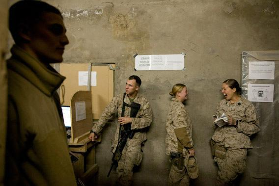 Lance Corporal Kristi Baker, 21, (L) shares a laugh with Hospital Corpsman Shannon Crowley, 22, US Marine with the FET (Female Engagement Team) 1st Battalion 8th Marines, Regimental Combat team II  while they stand in line to use the internet at their forward operating base on November 12, 2010 in Musa Qala, Afghanistan.