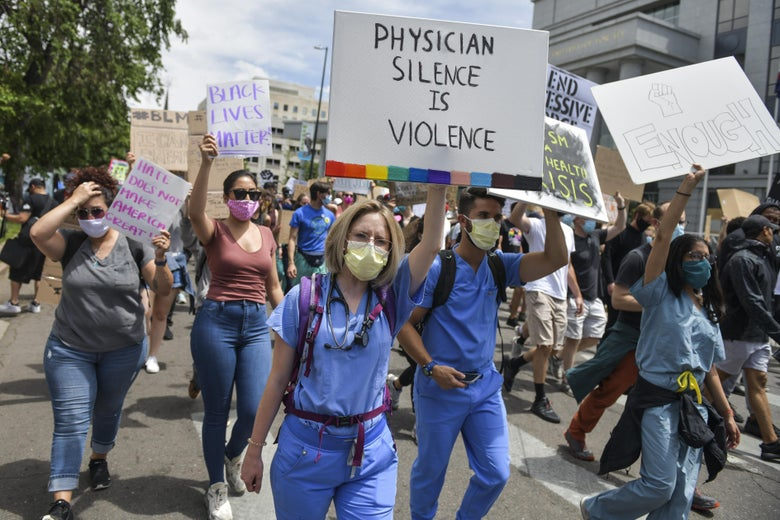 """Physicians in scrubs march with other Black Lives Matter protesters. One physician holds a sign that says """"Physician silence is violence."""""""