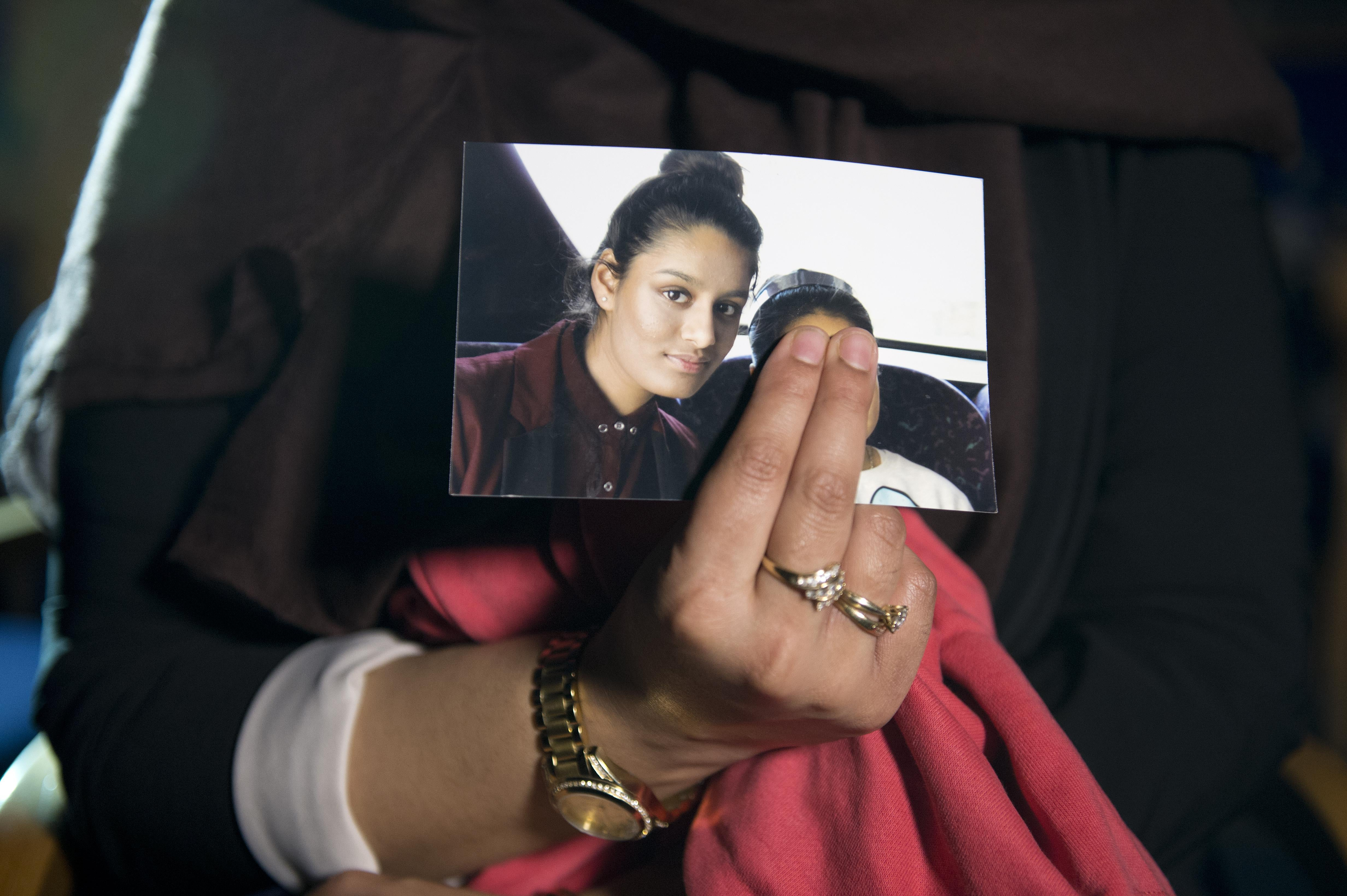 Renu Begum, eldest sister of Shamima Begum, 15, holds her sister's photo as she is interviewed by the media at New Scotland Yard on February 22, 2015 in London, England.