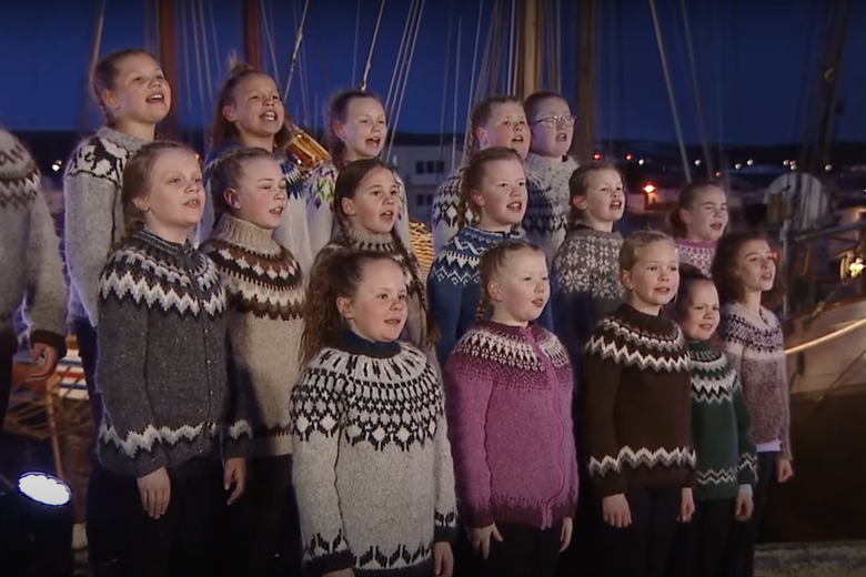 A choir of extremely blonde children sing in an Icelandic harbor