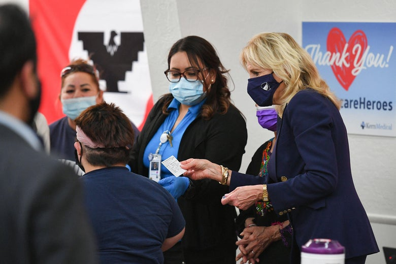Masked health care workers standing next to Jill Biden, who holds a vaccination card.