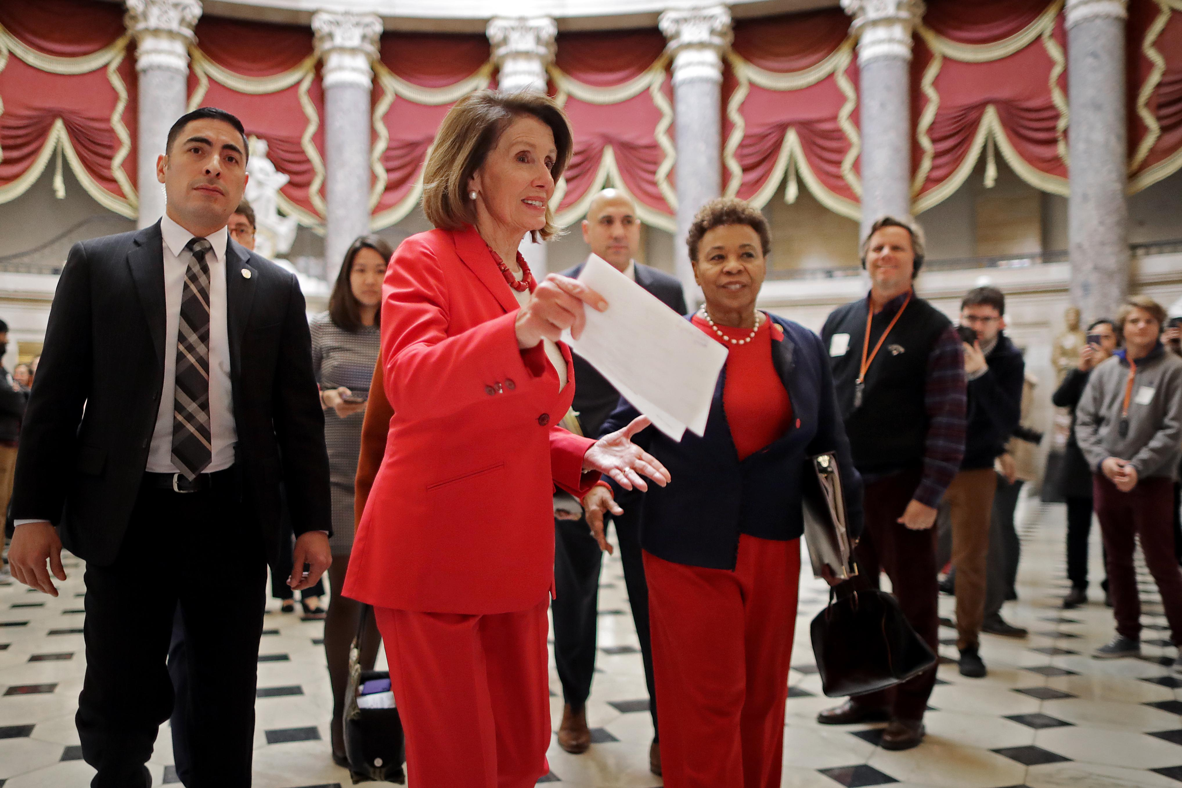 Nancy Pelosi holds a paper in her hand as she walks, followed by a crowd, toward the House floor.