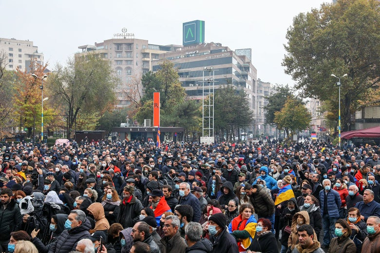 A crowd of people, mostly wearing masks, in an urban center.