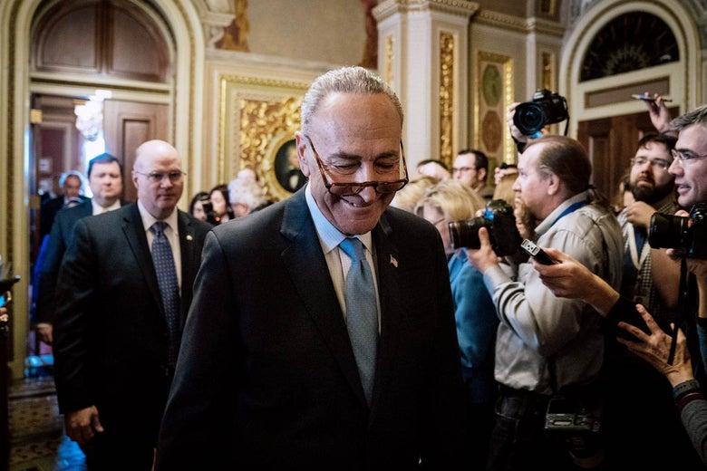 Chuck Schumer smiles as he passes a crowd of photographers and reporters at the Capitol.