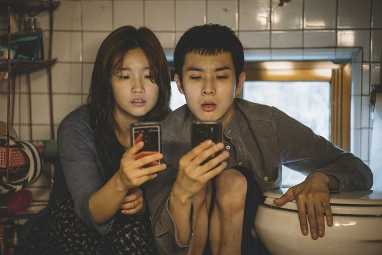 Park So-dam and Choi Woo-shik crouch next to a toilet, looking at their phones.