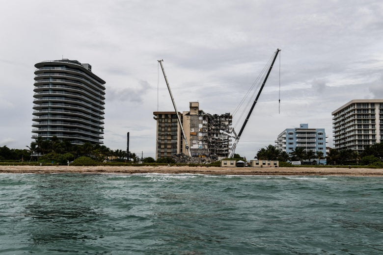 The partially collapsed Champlain Towers South condo between other condo buildings on the oceanfront seen from the water