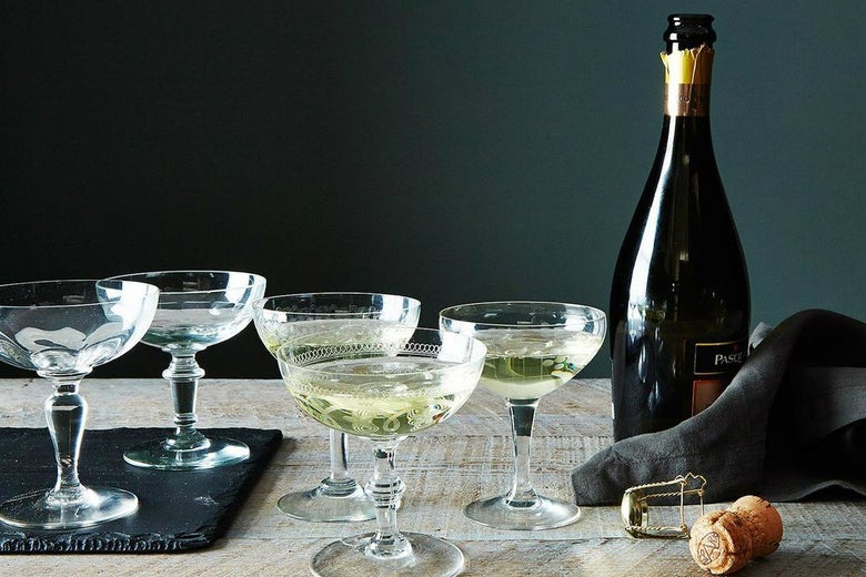 Uncorked bottle of sparkling wine next to five Champagne coupes, three of them full of bubbly