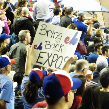 """A fan holds a sign reading, """"Bring Back Expos."""""""