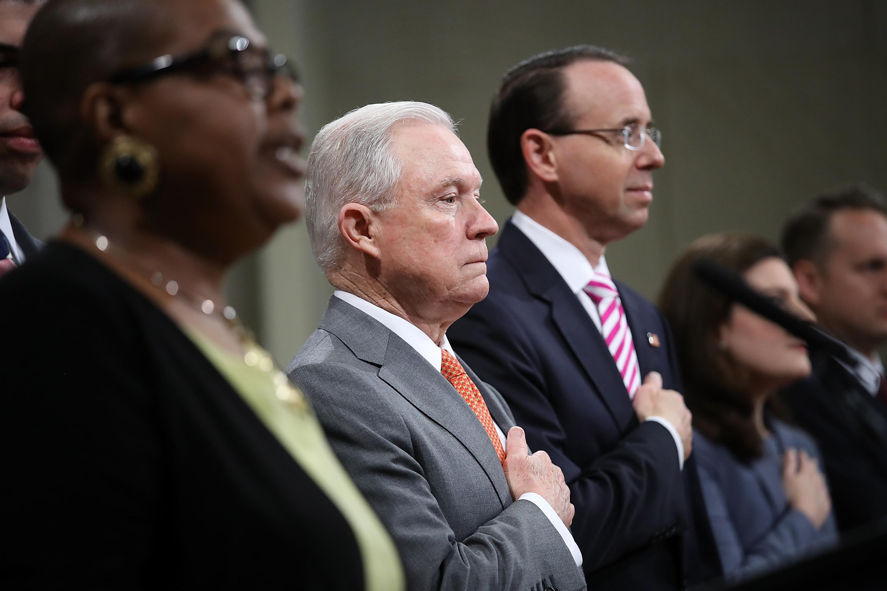Jeff Sessions, standing to the left of Deputy Attorney General Rod Rosenstein, places his hand over his heart.