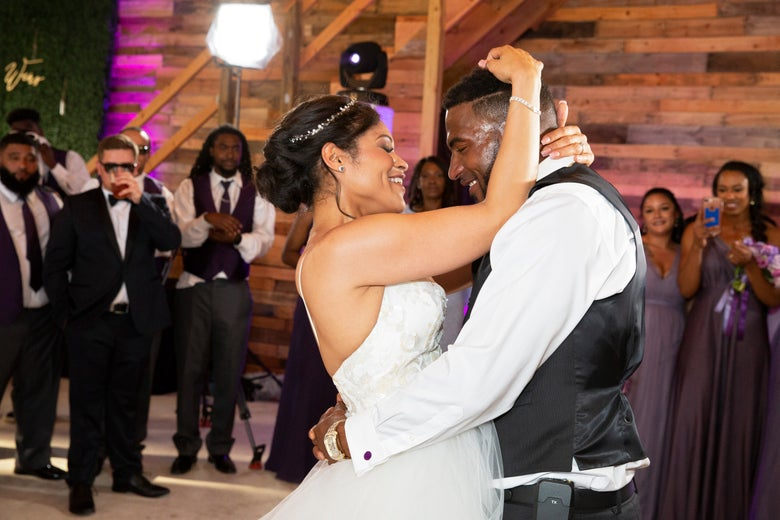 Marcus Martin and Marissa Blair dance amid wedding guests at their wedding reception.